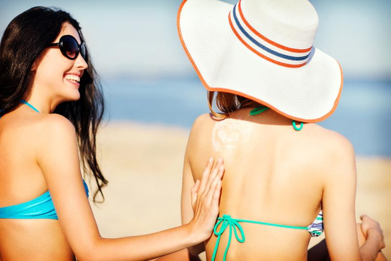 37679072-summer-holidays-and-vacation-girls-applying-sun-protection-cream-on-the-beach-Stock-Photo.jpg
